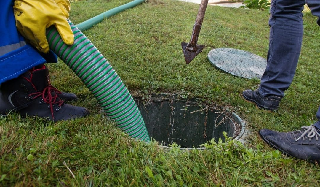 Two people pumping a septic tank